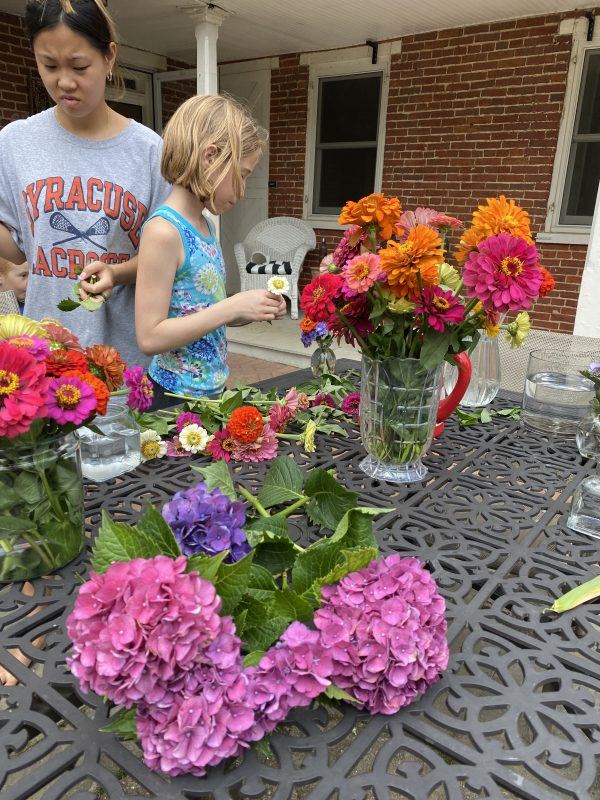 stunning colors of flowers being arranged. on a hot day at the patio table