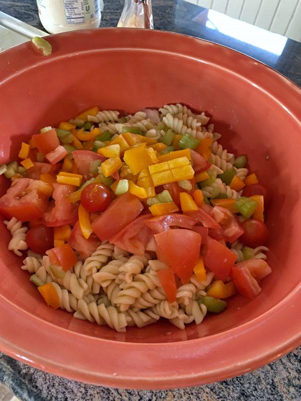 Adding choppedcheese nd vegetables to large orange bowl for tuna pasta salad