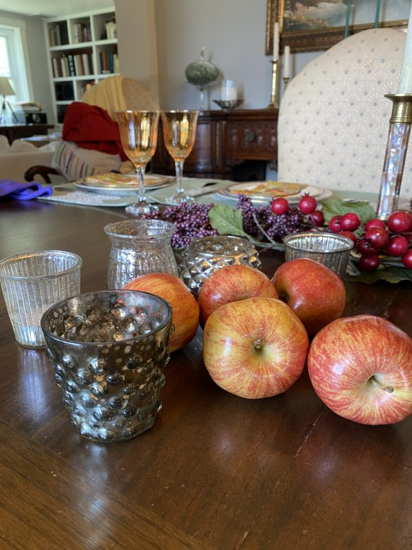 fall tablescape elements purple clusters and red berry faux stems, apples,mercury glass votives, candlesticks,pottery pieces