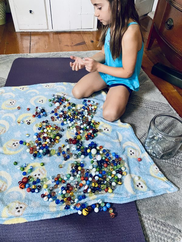 Sorting marbles on a small blanket by size and color