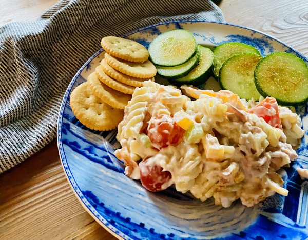 Tuna Pasta Salad is served on blue and white luncheon plate with Ritz crakers adn cucumber slices