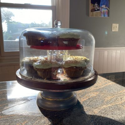 carrot cupcake in cake stand with glass cover