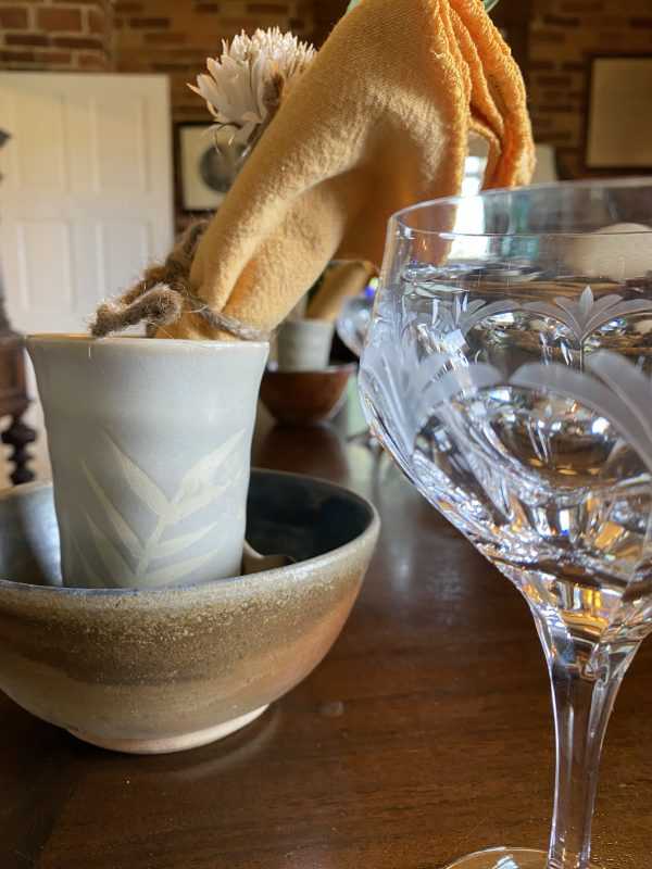 Place Setting for Rustic Autumn Tablescape with crystal wine glass, pottery bowl adn gold napkin