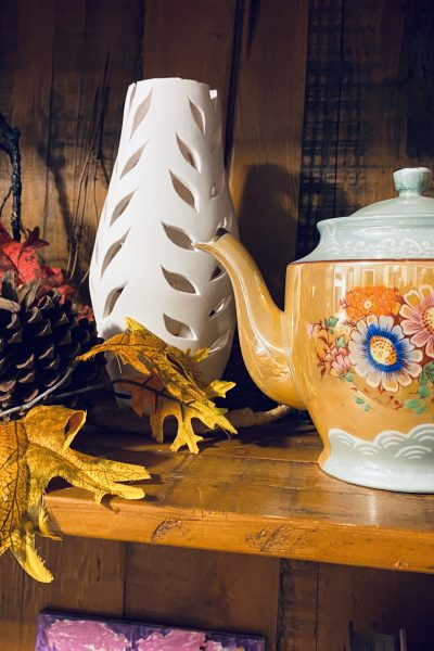 Tea Pot Close Up on shelf with white vase and leaves
